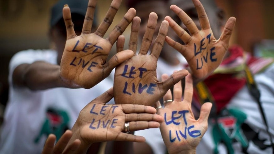 "Demonstrators show the message ""Let Live"" on the palms of their hands as they take part in the ""Global March for Elephants and Rhinos"" to raise awareness for their plight, in Nairobi, Kenya Saturday, Oct. 4, 2014. Organisers of the global march, which they hope will take place in over 100 cities across the world, say it is a collaboration between many wildlife conservation organisations aiming to save elephants and rhinos from extinction by poachers and call for a ban on the trade of ivory and rhino horn. (AP Photo/Ben Curtis)"