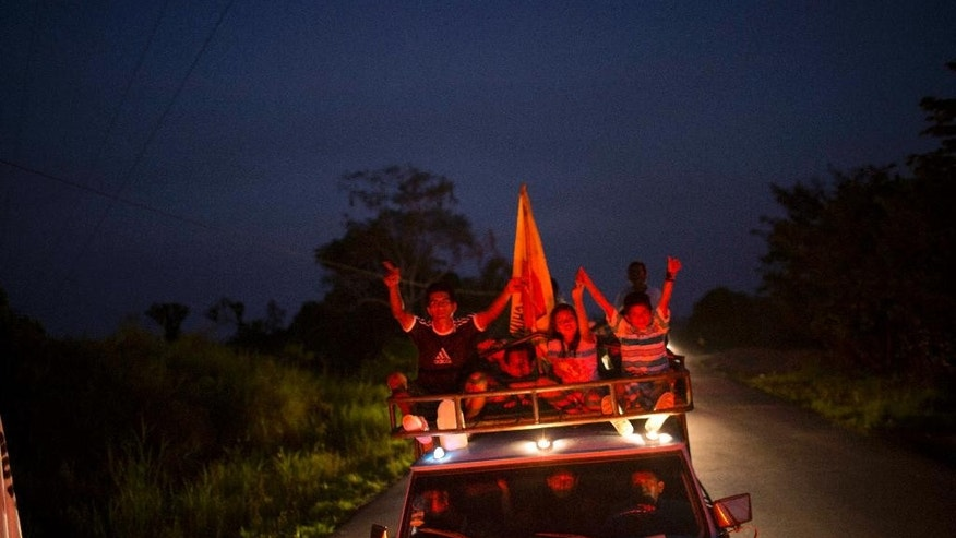 "In this Sept. 25, 2014 photo, supporters of Ucayali gubernatorial candidate Manuel Gambini, caravan through the rural roads of Irazola, Peru. In his run for governor Gambini has repeatedly cited his plaudits from the U.S. government for promoting the cultivation of cocoa beans over coca leaves in this cocaine-producing hotspot. But the man the U.S. Agency for International Development held up as recently as 2012 as a ""dynamic new partner"" is now under investigation for money laundering, having amassed a curious-sized fortune despite a small mayoral salary. (AP Photo/Rodrigo Abd)"