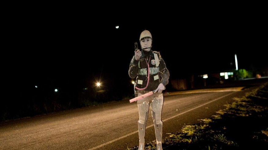 "In this Sept. 26, 2014 photo, as a reminder to criminals that police are in the area, a cutout of a policewoman is seen on the highway that connects the Peruvian towns of Aucayacu and Tocache. ""We are now a despicable reflection of what Colombia was - and what Mexico is today,"" said Sonia Medina, Peru's public prosecutor for drug enforcement. Peru is far less violent, but drug-related murders have been on the rise since the mid-2000s, when Colombian and Mexican traffickers began arriving in greater numbers. (AP Photo/Rodrigo Abd)"