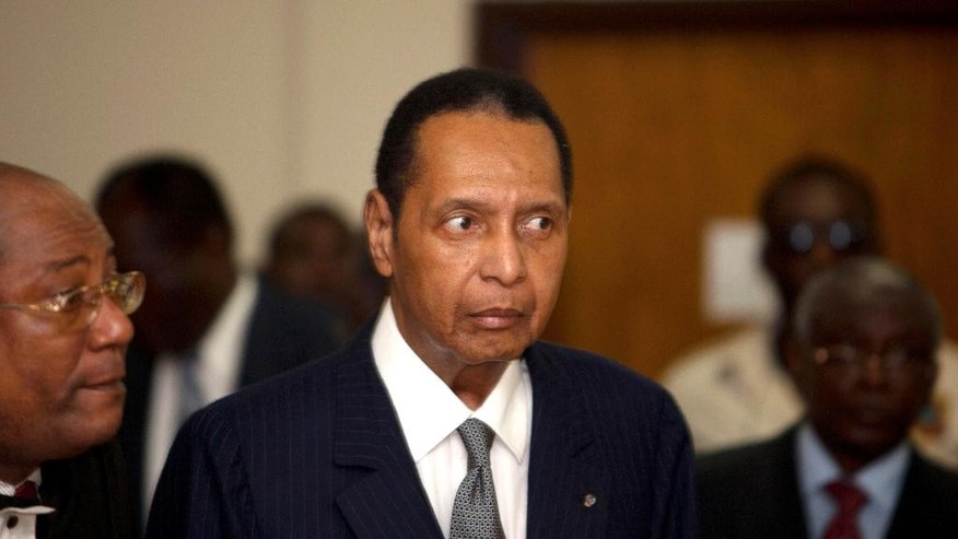 "FILE - In this file photo dated Feb. 28, 2013, former Haitian dictator Jean-Claude Duvalier, known as ""Baby Doc,"" attends his hearing at court in Port-au-Prince, Haiti, as Haitian authorities charged Duvalier with human rights abuses and embezzlement but a judge ruled he should face charges only for the alleged financial crimes. It is announced Saturday Oct. 4, 2014, that Haitian ex-dictator Jean-Claude Duvalier has died of a heart attack. (AP Photo/Dieu Nalio Chery, FILE)"