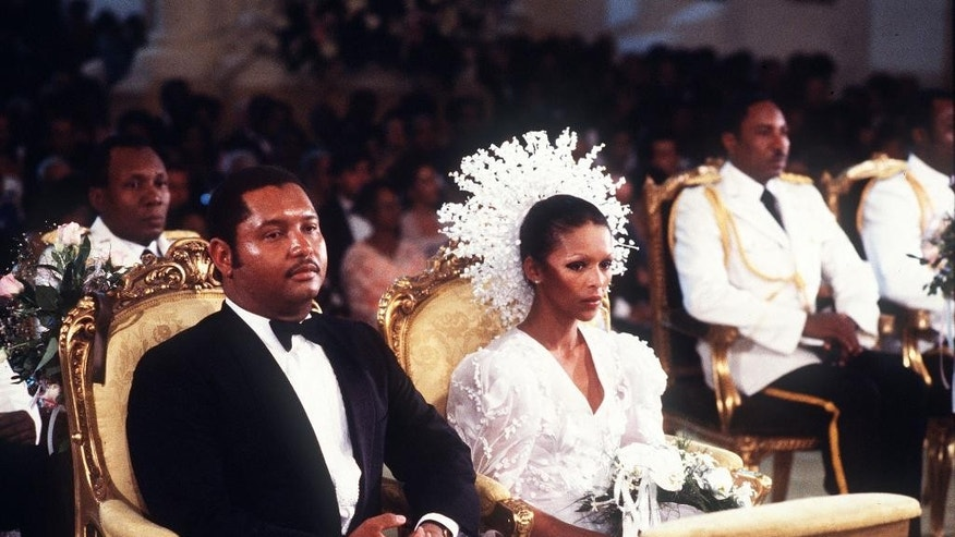 "FILE - In this May 27, 1980 file photo, then Haitian president Jean-Claude Duvalier, left, is pictured with his bride,  Michele Bennett, during their wedding ceremony in the Port-au-Prince National Cathedral in Haiti.  Duvalier, the self-proclaimed ""president for life"" of Haiti whose corrupt and brutal regime sparked a popular uprising that sent him into a 25-year exile, died Saturday, Oct. 4, 2014 of a heart attack, his attorney said.  He was 63.  (AP File Photo)"