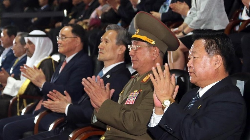 North Korea's National Defense Commission Vice Chairman Hwang Pyong So, second right, and Choe Ryong Hae, right, North Korea's ruling Workers Party secretary, clap with South Korean Prime Minister Chung Hong-won and South Korean President Park Geun-hye's National Security Adviser Kim Kwan-jin, third from right, during the closing ceremony for the 17th Asian Games in Incheon, South Korea, Saturday, Oct. 4, 2014. Hwang, North Korea's presumptive No. 2, and other members of Pyongyang's inner circle met with South Korean officials Saturday in the rivals' highest level face-to-face talks in five years, a possible indication that both sides are interested in pursuing better ties after months of animosity. (AP Photo/Yonhap, Bae Jae-man) KOREA OUT