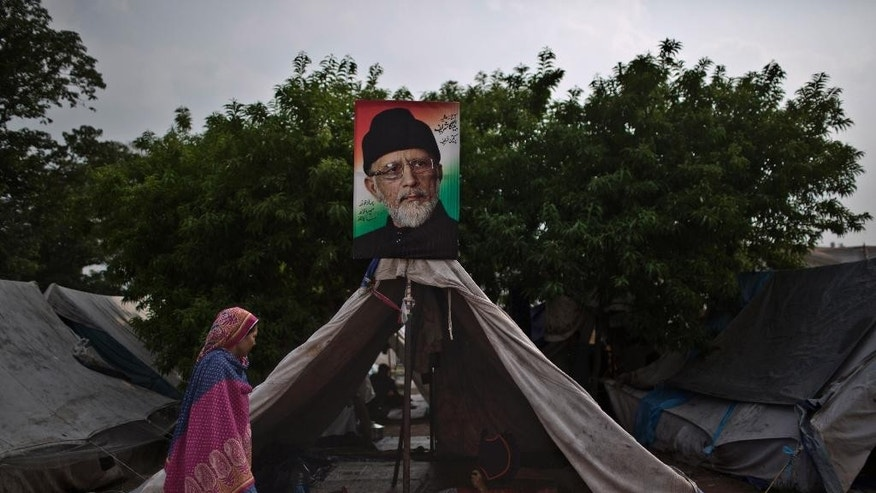 An anti-government protester, talks with a youth laying inside a tent decorated with a poster showing Muslim cleric Tahir-ul-Qadri, near the parliament building, where they are camping, in Islamabad, Pakistan, Saturday, Oct. 4, 2014. Anti-government demonstrators led by opposition politicians Imran Khan and Muslim cleric Tahir-ul-Qadri converged on the capital in mid-August, demanding Prime Minister Nawaz Sharif's ouster over alleged fraud in last year's election. Sharif told the parliament that the protests have damaged the image of Pakistan in the world and also caused huge economic losses in the country. (AP Photo/Muhammed Muheisen)
