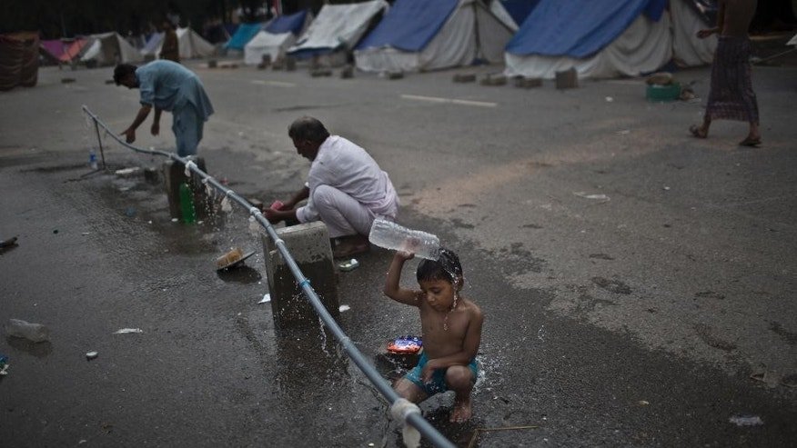 A Pakistani boy, whose family is taking part in anti-government protests near the parliament building, pours water on himself next to other protesters, where they are camping, in Islamabad, Pakistan, early Saturday, Oct. 4, 2014. Anti-government demonstrators led by opposition politicians Imran Khan and Muslim cleric Tahir-ul-Qadri converged on the capital in mid-August, demanding Prime Minister Nawaz Sharif's ouster over alleged fraud in last year's election. Sharif told the parliament that protestors have damaged the image of Pakistan in the world and also caused huge economic losses in the country. (AP Photo/Muhammed Muheisen)