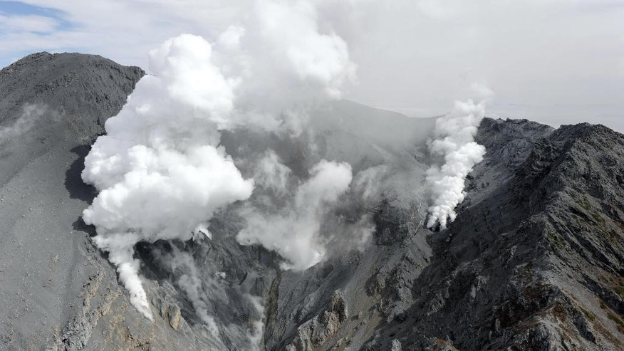 White plumes of gases and ash are spewed out from the summit crater of Mount Ontake in central Japan, Saturday morning, Oct. 4, 2014. Rescuers on Saturday retrieved four more bodies near the summit of the Japanese volcano that erupted last weekend, raising the death toll to 51, authorities said. (AP Photo/Kyodo News) JAPAN OUT, MANDATORY CREDIT
