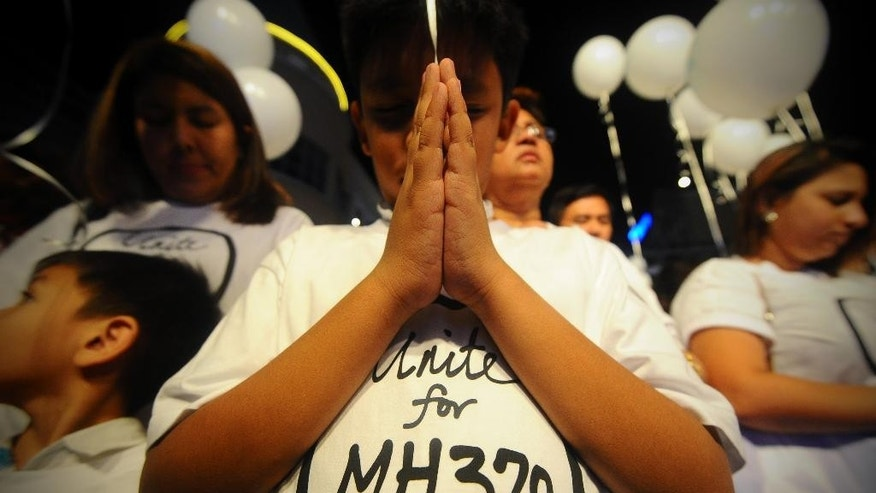 FILE - In this March 18, 2014 photo, a young Malaysian boy prays, at an event for the missing Malaysia Airline Flight 370, at a shopping mall, in Petaling Jaya,  on the outskirts of Kuala Lumpur, Malaysia.  After a four-month hiatus, the hunt for Malaysia Airlines Flight 370 is about to resume in a desolate stretch of the Indian Ocean, with searchers lowering new equipment deep beneath the waves in a bid to finally solve one of the world's most perplexing aviation mysteries.  (AP Photo/Joshua Paul, File)