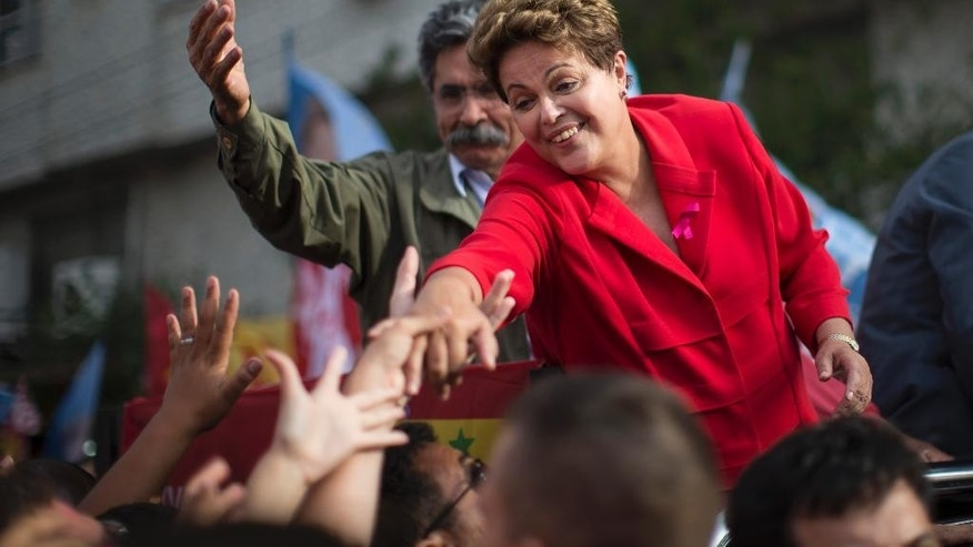 Brazil's President Dilma Rousseff, presidential candidate for re-election of the Workers Party, PT, greets supporters during a campaign rally in Porto Alegre, Brazil, Saturday, Oct. 4, 2014. Brazil will hold general elections on Oct. 5. (AP Photo/Felipe Dana)