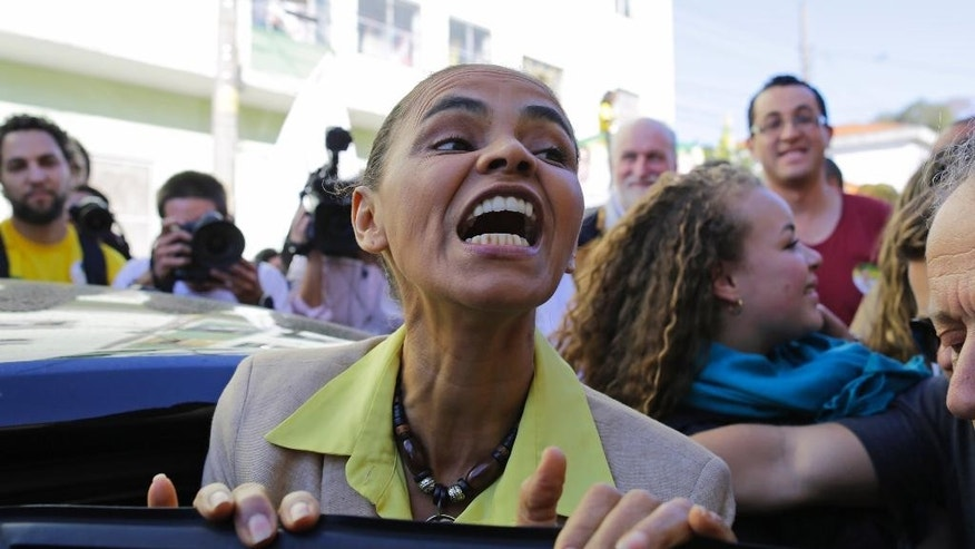 Marina Silva, presidential candidate of the Brazilian Socialist Party, PSB, talks with supporters as she leaves after a campaign rally in Sao Paulo, Brazil, Saturday, Oct. 4, 2014. Brazil will hold general elections on Oct. 5. (AP Photo/Nelson Antoine)