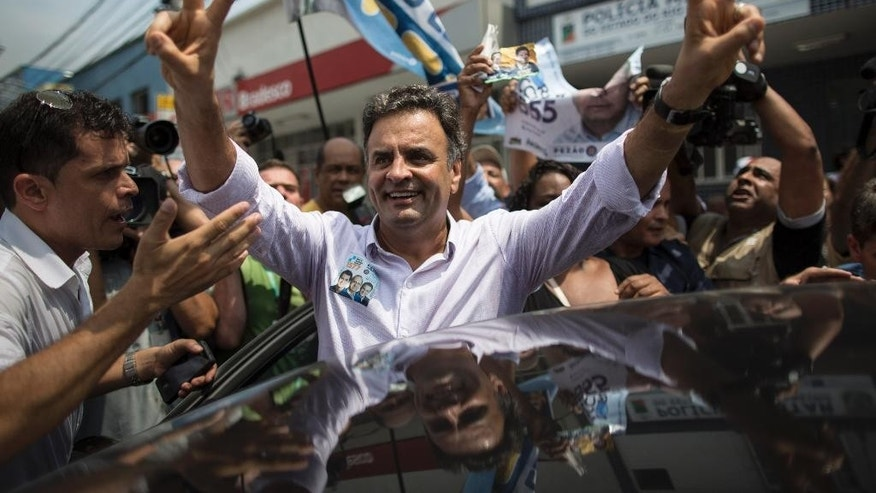 """FILE - In this Sept. 30, 2014 file photo, Aecio Neves, presidential candidate of the Brazilian Social Democracy Party, PSDB, flashes a victory sign as he campaigns at the """"Mercadao de Madureira,"""" or Madureira Market in Rio de Janeiro, Brazil. Brazil will hold general elections on Oct. 5. (AP Photo/Felipe Dana, File)"""