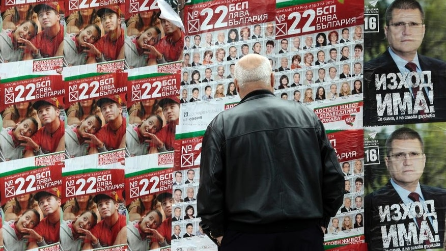A man looks at pre-election posters of the Bulgarian Socialist's party in Sofia, Friday, Oct. 3, 2014. Bulgarians are voting Sunday in early parliamentary elections that will determine whether the country decides to continue with the construction of a controversial Russian gas pipeline, a project the European Union opposes due to the added leverage it would give the Kremlin over Europe's energy market. (AP Photo/Valentina Petrova)