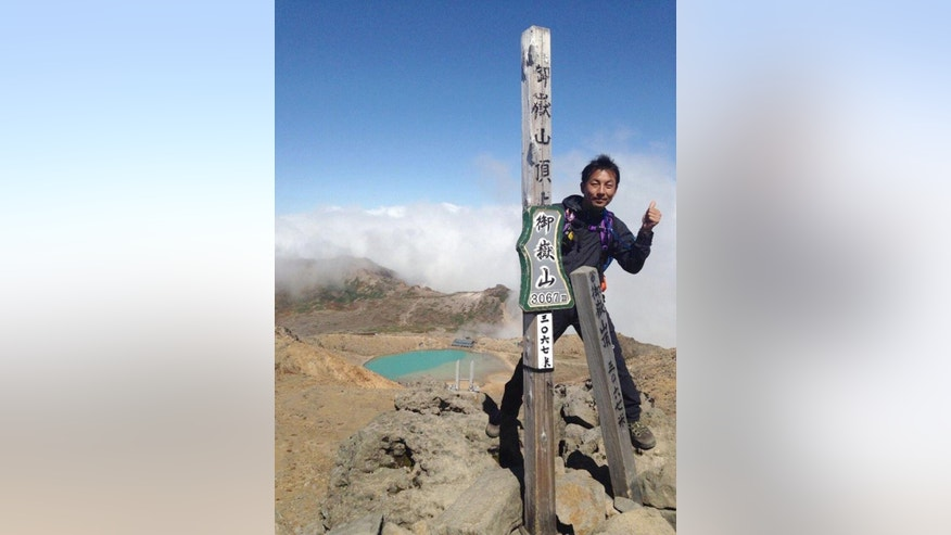 In this Saturday, Sept. 27, 2014 photo found in a smart phone possessed by 41-year-old hiker Hideomi Takahashi who fell victim to the eruption of Mount Ontake, and was uploaded on twitter by his friend Thursday, Oct. 2, Takahashi poses on the summit of Mount Ontake four minutes before the initial eruption of the volcanic mountain in central Japan. More than 50 people died when Mount Ontake, a popular hiking destination in central Japan, erupted without warning on Sept. 27 in the country's deadliest volcanic eruption since World War II. Together, they paint a typical picture of weekend recreational hikers in Japan. A few children and senior citizens, but mostly middle-aged working people enjoying the first Saturday of the fall foliage season.   (AP Photo/Courtesy Hideomi Takahashi)  EDITORIAL USE ONLY, NO SALES, JAPAN OUT