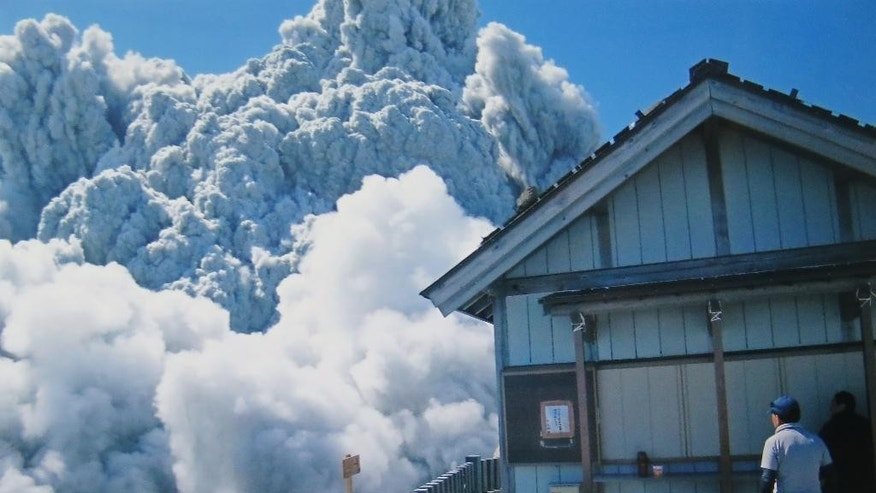 FILE - In this Saturday, Sept. 27, 2014 file photo taken by 59-year-old hiker Izumi Noguchi who fell victim to the eruption of Mount Ontake, and was offered to Kyodo News by his wife, Hiromi, Friday, Oct. 3, a hiker standing on the summit shrine compound on Mount Ontake watches dense plumes of gases and ash billowing from the crater as the volcanic mountain starts to erupt in central Japan. Construction company employee Noguchi was climbing alone, as his usual hiking companion, his wife Hiromi, had to work, she told Japanese broadcaster NHK and other media. His compact camera was banged up, but the memory chip inside was undamaged. She printed all 100 shots. (AP Photo/Kyodo News, Izumi Noguchi, File) JAPAN OUT, MANDATORY CREDIT