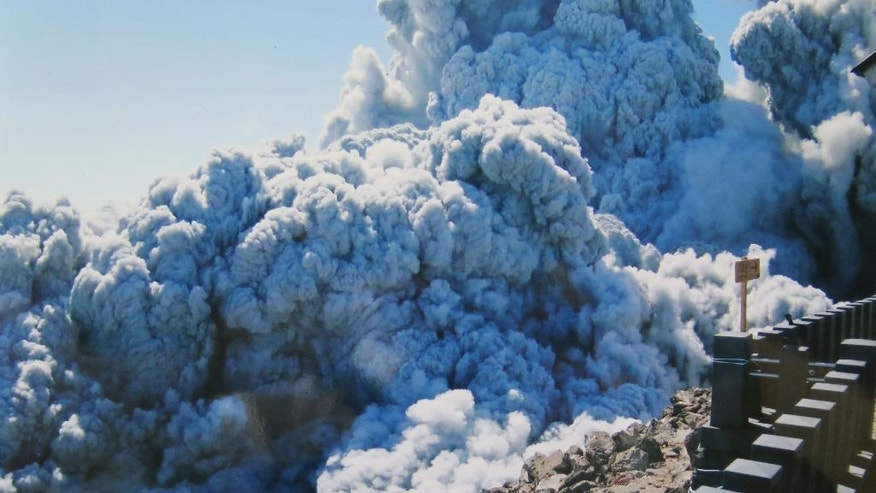 FILE - In this Saturday, Sept. 27, 2014 file photo taken by 59-year-old hiker Izumi Noguchi who fell victim to the eruption of Mount Ontake, and was offered to Kyodo News by his wife, Hiromi, Friday, Oct. 3, dense plumes of gases and ash billow from the summit crater of Mount Ontake as the volcanic mountain starts to erupt in central Japan. Construction company employee Noguchi was climbing alone, as his usual hiking companion, Hiromi, had to work, she told Japanese broadcaster NHK and other media. His compact camera was banged up, but the memory chip inside was undamaged. She printed all 100 shots. (AP Photo/Kyodo News, Izumi Noguchi, File) JAPAN OUT, MANDATORY CREDIT