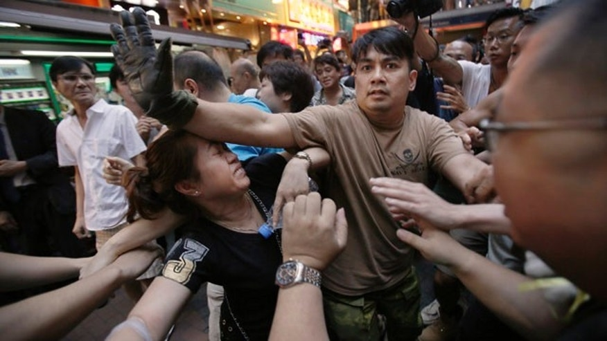 October 4, 2014: A woman is protected from the crowd by pro-democracy student protesters after a scuffle with local residents in Mong Kok, Hong Kong. Friction between pro-democracy protesters and opponents of their weeklong occupation of major Hong Kong streets persisted Saturday as police denied they had any connection to criminal gangs suspected of inciting attacks on largely peaceful demonstrators. (AP Photo/Wally Santana)