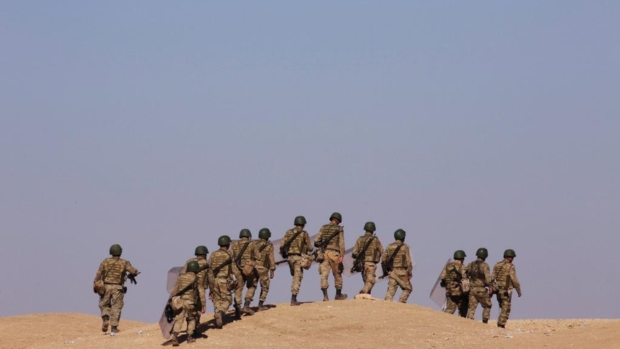 Turkish soldiers walk to their positions on a hill top at Mursitpinar near Suruc, at the Turkey-Syria border, overlooking Kobani in Syria as fighting intensified between Syrian Kurds and the militants of Islamic State group, Sunday, Oct. 5, 2014. (AP Photo/Lefteris Pitarakis)