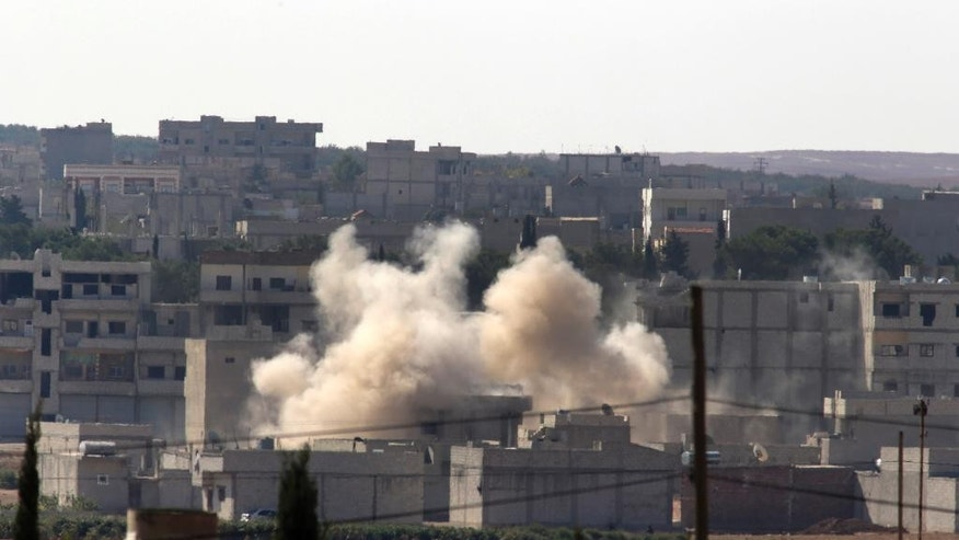 Smoke rises after a shell landed in Kobani in Syria as fighting intensified between Syrian Kurds and the militants of Islamic State group, as seen from Mursitpinar near Suruc, at the Turkey-Syria border, Sunday, Oct. 5, 2014.  (AP Photo/Lefteris Pitarakis)