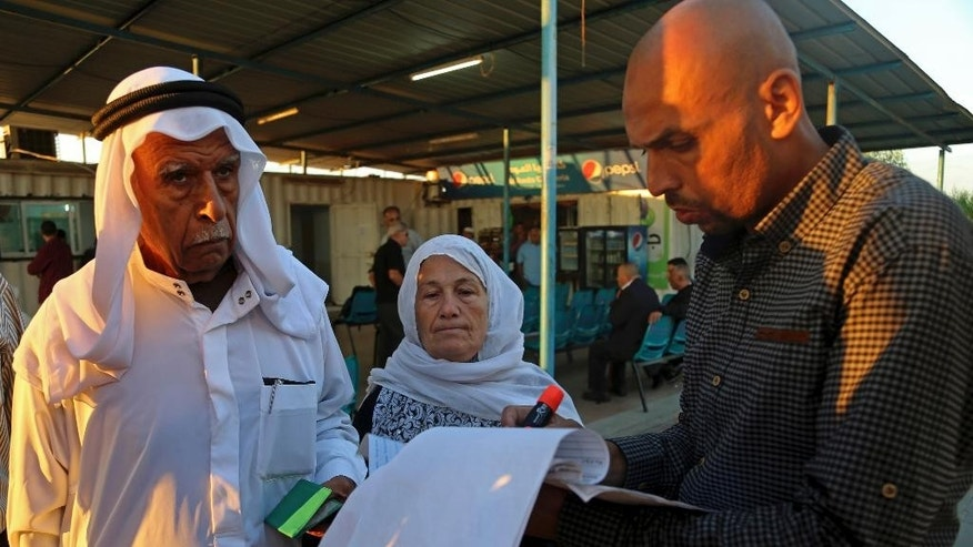 A Palestinian worker checks a list of  names of registered Muslim pilgrims who are waiting to cross the Erez border crossing between Israel and Gaza headed to Jerusalem during the three-day holiday of Eid al-Adha, in the northern Gaza Strip, Sunday, Oct. 5, 2014. In a rare gesture, Israeli authorities relaxed restrictions and allowed 550 Palestinian pilgrims to cross into Israel from Gaza to pray at the al-Aqsa mosque in Jerusalem. The  men had to be over 60 years old. (AP Photo/Adel Hana)