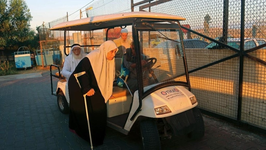 Elderly Palestinian pilgrims ride an electronic car to cross the Erez border crossing between Israel and Gaza heading to Jerusalem during the three-day Muslim holiday of Eid al-Adha, in the northern Gaza Strip, Sunday, Oct. 5, 2014. In a rare gesture, Israeli authorities relaxed restrictions and allowed 550 Palestinian pilgrims to cross into Israel from Gaza to pray at the al-Aqsa mosque in Jerusalem. The  men had to be over 60 years old. (AP Photo/Adel Hana)