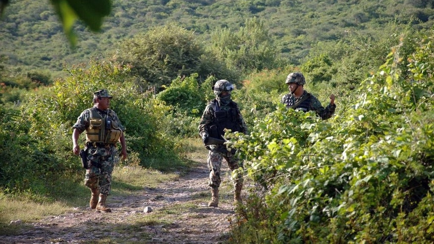 Mexican marines guard the road that leads to the site where an alleged clandestine mass grave was found near the city of Iguala, Mexico,  Saturday Oct. 4, 2014. Mexican officials said a clandestine grave holding an undetermined number of bodies was found outside a town where violence last weekend resulted in six deaths and the disappearance of 43 students. (AP Photo/Alejandrino Gonzalez)
