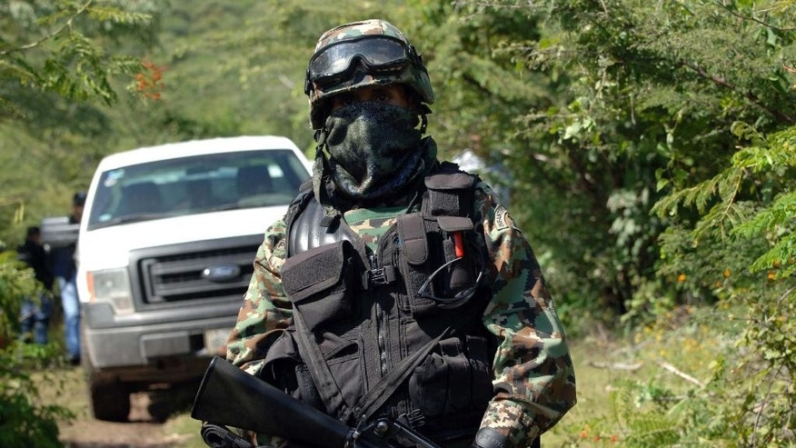 A Mexican navy marine guards the road that leads to the site where an alleged clandestine mass grave was found near the city of Iguala, Mexico, Saturday Oct. 4, 2014.  Mexican officials said a clandestine grave holding an undetermined number of bodies was found outside a town where violence last weekend resulted in six deaths and the disappearance of 43 students. (AP Photo/Alejandrino Gonzalez)