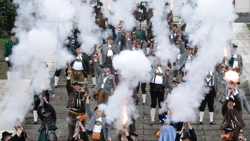 Bavarian riflemen and women in traditional costumes fire their muzzle loaders in front of the 'Bavaria' statue on the last day of the Oktoberfest beer festival in Munich, southern Germany, Sunday, Oct. 5, 2014. (AP Photo/Matthias Schrader)