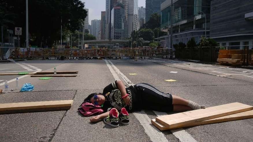 A lone pro-democracy student protester sleeps in the middle of an occupied road in Hong Kong, Sunday, Oct. 5, 2014. Bolstered by a massive rally overnight, Hong Kong's pro-democracy activists were defiant on the eighth day of protests Sunday in the face of attacks by opponents and government warnings to clear the business district streets they have occupied to press their demand for reforms. (AP Photo/Wally Santana)