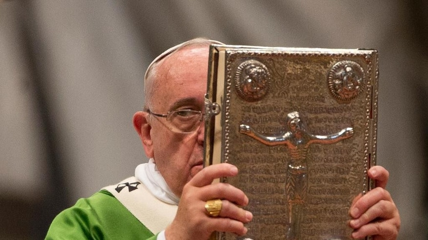 Pope Francis hoists the Gospel book as he celebrates a mass in St. Peter's Basilica at the Vatican, Sunday, Oct. 5, 2014 to open the extraordinary Synod on the family. Pope Francis on Sunday opened a two-week meeting of bishops and cardinals from around the world aimed at making the church's teaching on family life — marriage, sex, contraception, divorce and homosexuality — relevant to today's Catholic families. (AP Photo/Alessandra Tarantino)