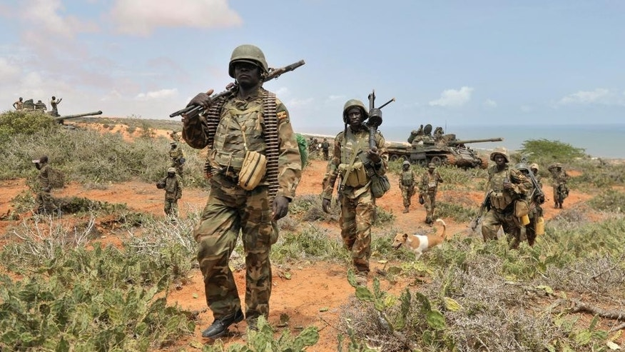 In this photo taken Sunday, Oct. 5, 2014 and provided by the African Union Mission to Somalia (AMISOM), African Union (AU) soldiers march along the top of a hill overlooking the al-Shabab stronghold of Barawe, a coastal town 220 kilometers (135 miles) southwest of Mogadishu, in Somalia. Officials in Somalia say AU and Somali troops have seized Barawe, the last major stronghold held by the Islamic militant group al-Shabab, with the AU claiming it as a significant victory because al-Shabab had used the port to bring in arms and fighters and export charcoal, a multi-million-dollar business. (AP Photo/AMISOM, Tobin Jones)