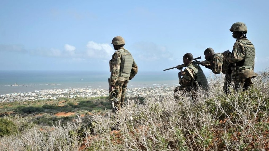 In this photo taken Sunday, Oct. 5, 2014 and provided by the African Union Mission to Somalia (AMISOM), African Union (AU) soldiers look for enemy combatants through the scope of a rifle on a hill overlooking the al-Shabab stronghold of Barawe, a coastal town 220 kilometers (135 miles) southwest of Mogadishu, in Somalia. Officials in Somalia say AU and Somali troops have seized Barawe, the last major stronghold held by the Islamic militant group al-Shabab, with the AU claiming it as a significant victory because al-Shabab had used the port to bring in arms and fighters and export charcoal, a multi-million-dollar business. (AP Photo/AMISOM, Tobin Jones)