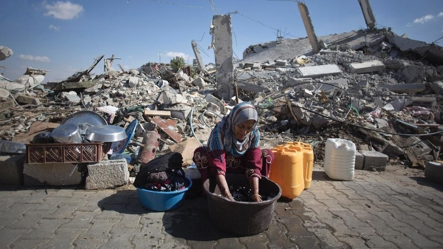 In this Wednesday, Oct. 1, 2014 photo, Palestinian woman washes clothes as she sits in front of the rubble of her family house in Khuzaa, southern of Gaza Strip. More than five weeks after the Israel-Hamas war in the Gaza Strip, tens of thousands of people whose homes were destroyed or badly damaged in the fighting still live in classrooms, storefronts and other crowded shelters. Yet despite their pressing needs, reconstruction efforts appear stymied by a continued Israeli-Egyptian border blockade of Gaza and an unresolved power struggle between the Islamic militant group Hamas and Western-backed Palestinian President Mahmoud Abbas. (AP Photo/Khalil Hamra)