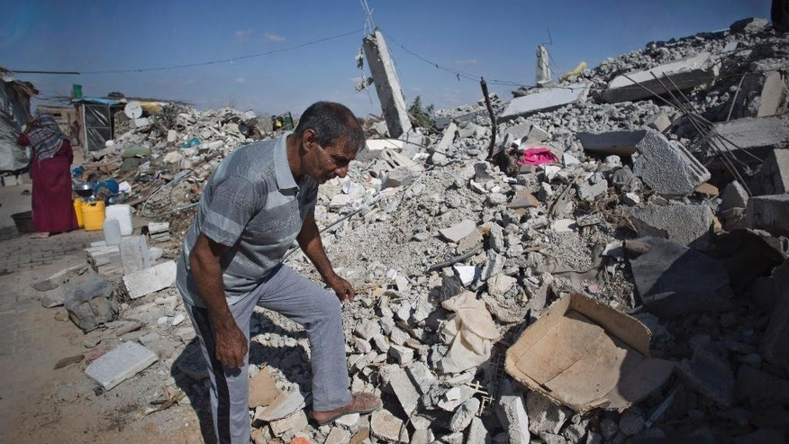 In this Wednesday, Oct. 1, 2014 photo, Palestinian Hamdan al-Najjar, looks in the rubble of his destroyed house in town of Khuzaa in the southern of Gaza Strip. More than five weeks after the Israel-Hamas war in the Gaza Strip, tens of thousands of people whose homes were destroyed or badly damaged in the fighting still live in classrooms, storefronts and other crowded shelters. Yet despite their pressing needs, reconstruction efforts appear stymied by a continued Israeli-Egyptian border blockade of Gaza and an unresolved power struggle between the Islamic militant group Hamas and Western-backed Palestinian President Mahmoud Abbas. (AP Photo/Khalil Hamra)
