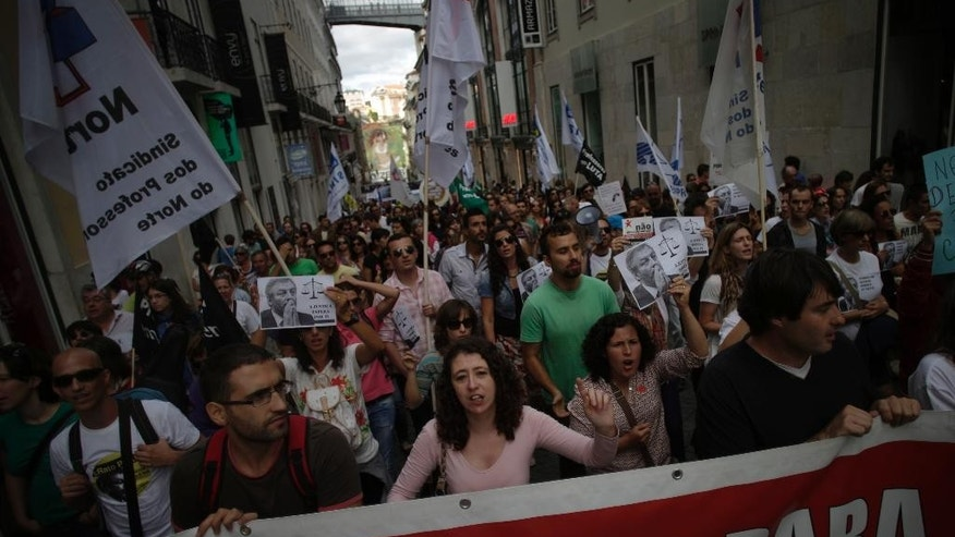 People shout slogans as they march during a protest by Portuguese teachers in Lisbon, Sunday, Oct. 5, 2014. Seven teachers' trade unions organised the march Sunday to protest the government's education policies. (AP Photo/Francisco Seco)