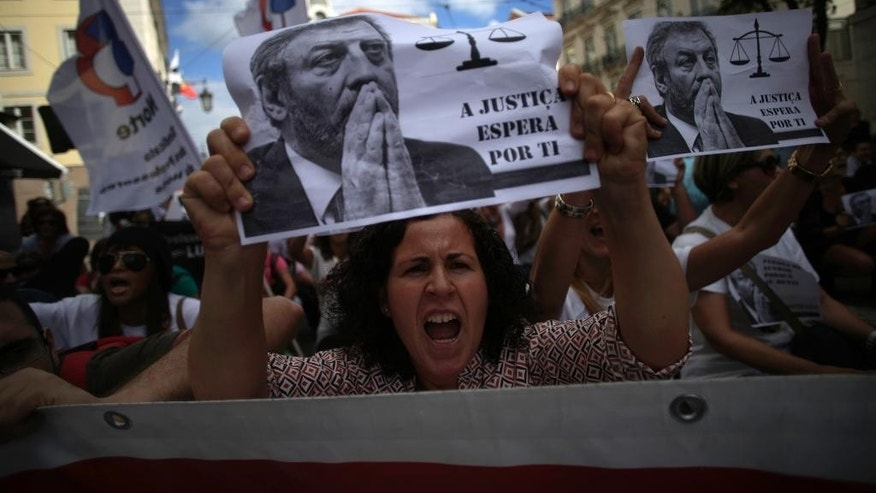 "A woman holding up a sheet of paper with the face of the Portuguese Education Minister Nuno Crato, shouts slogans during a protest by Portuguese teachers in Lisbon, Sunday, Oct. 5, 2014. Seven teachers' trade unions organised the march Sunday to protest the government's education policies. Sign reads in Portuguese: ""justice waits for you"" (AP Photo/Francisco Seco)"