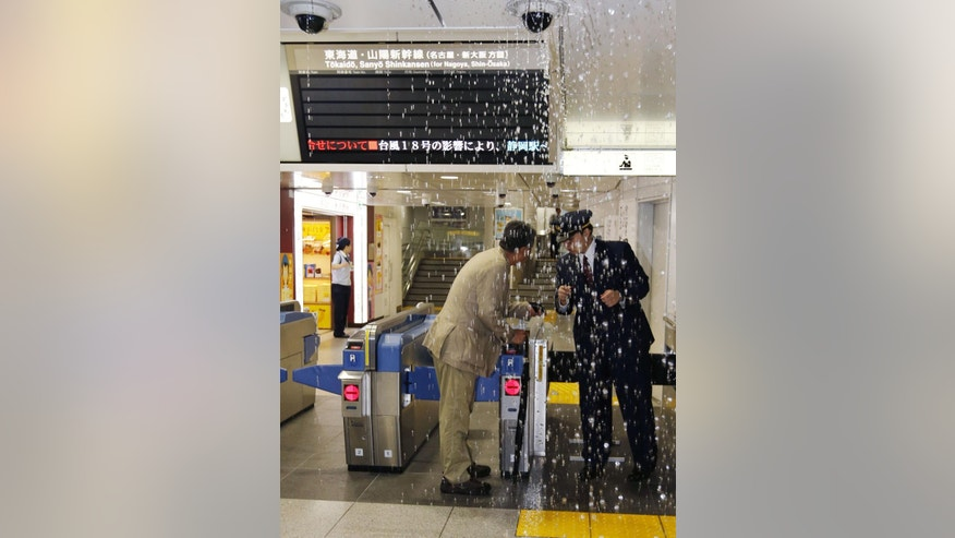 Rain leaks at Tokyo Station in Tokyo Monday, Oct. 6, 2014. A powerful typhoon made landfall in central Japan Monday morning after washing three American airmen in Okinawa out to sea the previous day, killing at least one. Bullet train service was suspended between Tokyo and Osaka because of heavy rain, and more than 600 flights were canceled at Tokyo's Haneda Airport. (AP Photo/Kyodo News) JAPAN OUT, MANDATORY CREDIT