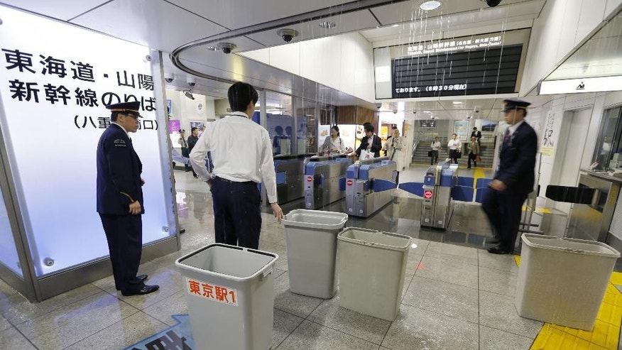 Japan Railways employments check water leak at Tokyo Station in Tokyo Monday, Oct. 6, 2014. A powerful typhoon made landfall in central Japan Monday morning after washing three American airmen in Okinawa out to sea the previous day, killing at least one. Bullet train service was suspended between Tokyo and Osaka because of heavy rain, and more than 600 flights were canceled at Tokyo's Haneda Airport. (AP Photo/Kyodo News) JAPAN OUT, MANDATORY CREDIT