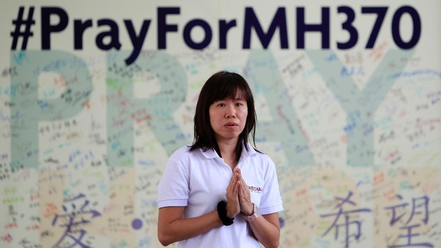 FILE - In this April 13, 2014 file photo, a member of Kechara Buddhist organization offers prayers for passengers onboard the missing Malaysia Airlines Flight 370 at Kechara Forest Retreat in Bentong, outside Kuala Lumpur, Malaysia. The hunt for Malaysia Airlines Flight 370 resumed Monday, Oct. 6, 2014 in a desolate stretch of the Indian Ocean, more than six months after the jet vanished. (AP Photo/Lai Seng Sin, File)
