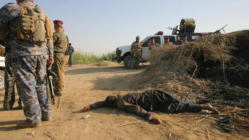 Iraqi security forces inspect the lifeless bodies of a militant from the Islamic State group after clashes, near the town of Jbala, about 35 miles (56 kilometers) south of Baghdad, Iraq, Saturday, Oct. 4, 2014. (AP Photo)