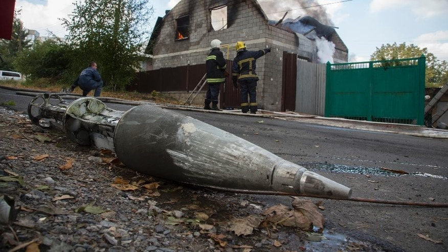 A fragment of a multiple missile 'Uragan', lies near a damaged private house after shelling in the town of Donetsk, eastern Ukraine Sunday, Oct. 5, 2014. According to rebels it comes from Ukrainian army's position. (AP Photo/Dmitry Lovetsky)