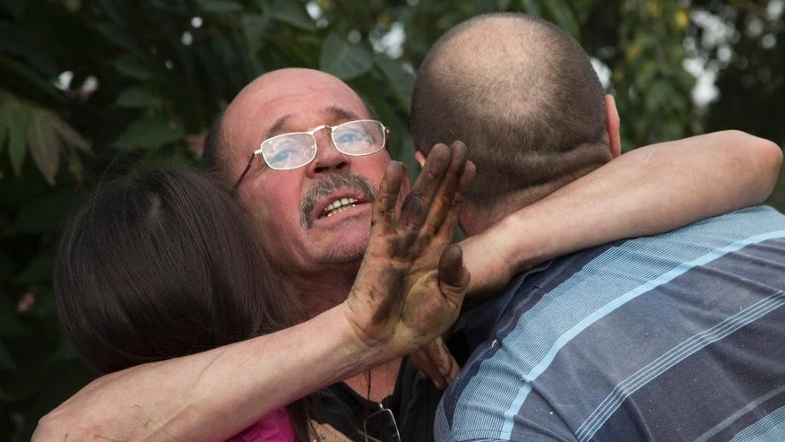 A man embraces his relatives after shelling in the town of Donetsk, eastern Ukraine Sunday, Oct. 5, 2014. (AP Photo/Dmitry Lovetsky)
