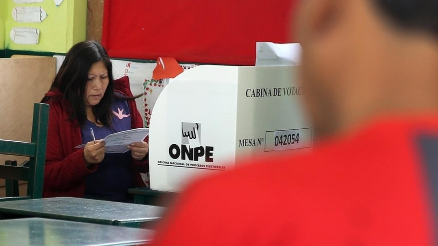 A woman casts her ballot during mayoral elections in Lima, Peru, Sunday, Oct. 5, 2014. Voters across Peru are choosing mayors, governors and municipal councils following the most violent campaign since 2000, with hundreds of candidates suspected of ties to drug trafficking. (AP Photo/Martin Mejia)