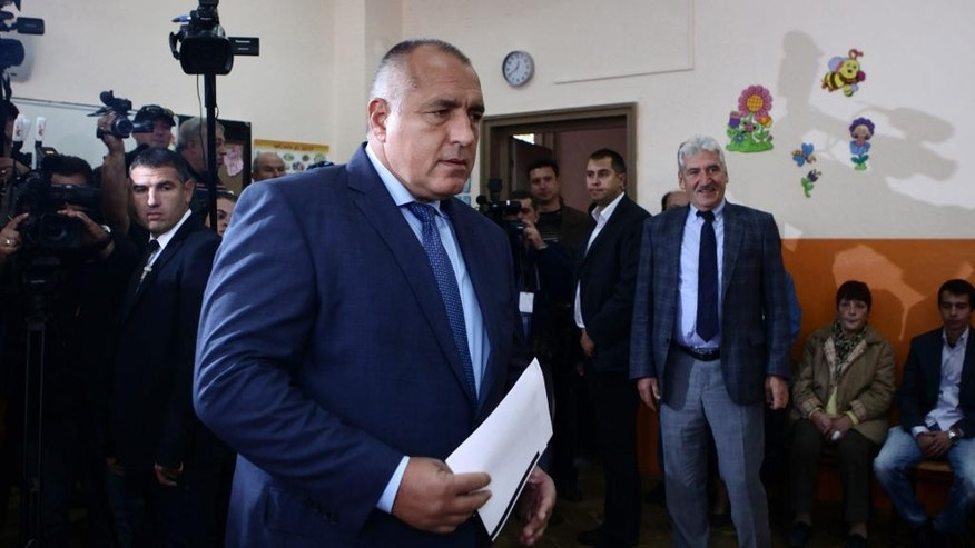 Boyko Borissov, former Bulgarian Prime Minister and leader of centre-right GERB party, holds his voting papers in Sofia, Sunday, Oct. 5, 2014. Opinion surveys predict the biggest vote winner will be center-right GERB party led by a former prime minister, Borisov, who says he would only continue building Bulgaria's part of the South Stream pipeline if the EU approved. Bulgarians are voting in a parliamentary election hoping a new government will end the political stalemate, revive the economy, solve a severe banking crisis, and find ways to ease Moscow's grip on the country's energy supplies. (AP Photo/STR)