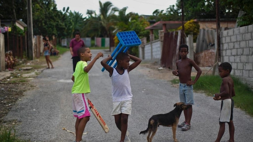 In this Sept. 29, 2014 photo, from left, Duani Rojas, Yoendry Díaz, Daniel Ordani, Yordeni Caballeros, gather in the street to start a game of cricket in the neighborhood of San Miguel del Padrón in Havana, Cuba, Monday, Sept. 29, 2014. Cuba's cricket partisans subsist on homemade and donated equipment from the embassies of cricket-playing countries. (AP Photo/Ramon Espinosa)