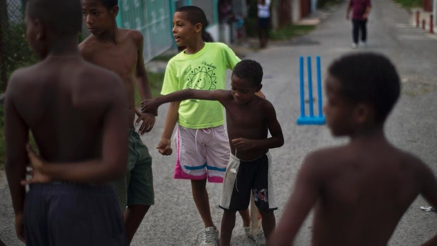 In this Sept. 29, 2014 photo, Yordeni Caballeros, center, chooses his teammates before a game of street cricket in the neighborhood of San Miguel del Padrón in Havana, Cuba, Monday, Sept. 29, 2014. Cricket is a part of the cultural identity of Caribbean migrant communities in Cuba, the descendants of some 250,000 workers from Jamaica, Dominica and other British colonies who moved to sugar towns in eastern Cuba where they attended Protestant churches, ate spicier food and played cricket. (AP Photo/Ramon Espinosa)