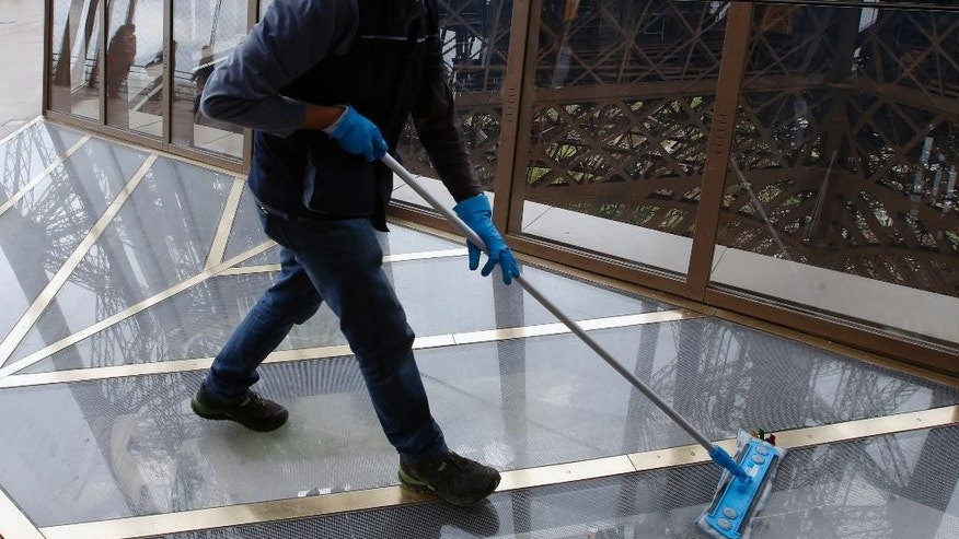 A worker cleans the new glass floor at The Eiffel Tower during the inauguration of the newly refurbish first floor, in Paris, France, Monday, Oct. 6, 2014. Visitors of the Eiffel Tower can walk on a transparent floor at 188 feet high and look down through solid glass, with safety glass barriers around the edge. (AP Photo/Francois Mori)