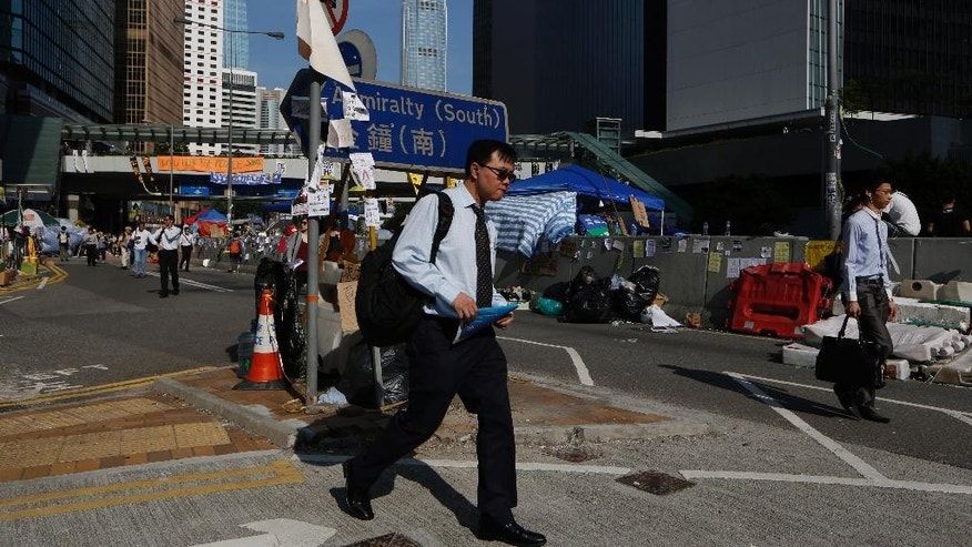 People walk to work on a main road in the occupied areas surrounding the government complex in Hong Kong Oct. 6, 2014. Hong Kong's civil servants returned to work and schools were reopening Monday as a massive pro-democracy protest that has occupied much of the city center for the week dwindled. (AP Photo/Kin Cheung)