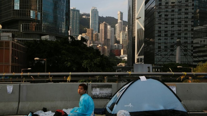 A pro-democracy protester sits on a roadside in the occupied areas surrounding the government complex in Hong Kong, Monday, Oct. 6, 2014. Hong Kong's civil servants returned to work and schools were reopening Monday as a massive pro-democracy protest that has occupied much of the city center for the week dwindled. (AP Photo/Kin Cheung)