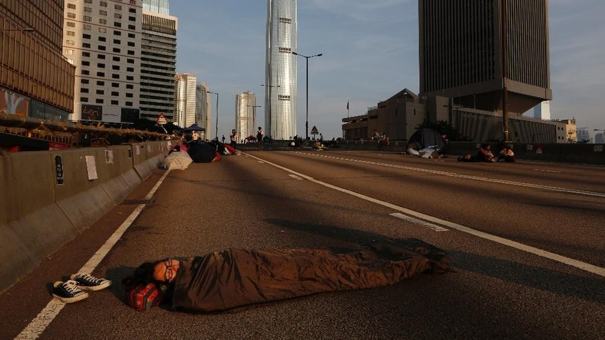 A pro-democracy protester sleeps on a roadside in the occupied areas surrounding the government complex in Hong Kong, Monday, Oct. 6, 2014. Hong Kong's civil servants returned to work and schools were reopening Monday as a massive pro-democracy protest that has occupied much of the city center for the week dwindled. (AP Photo/Kin Cheung)