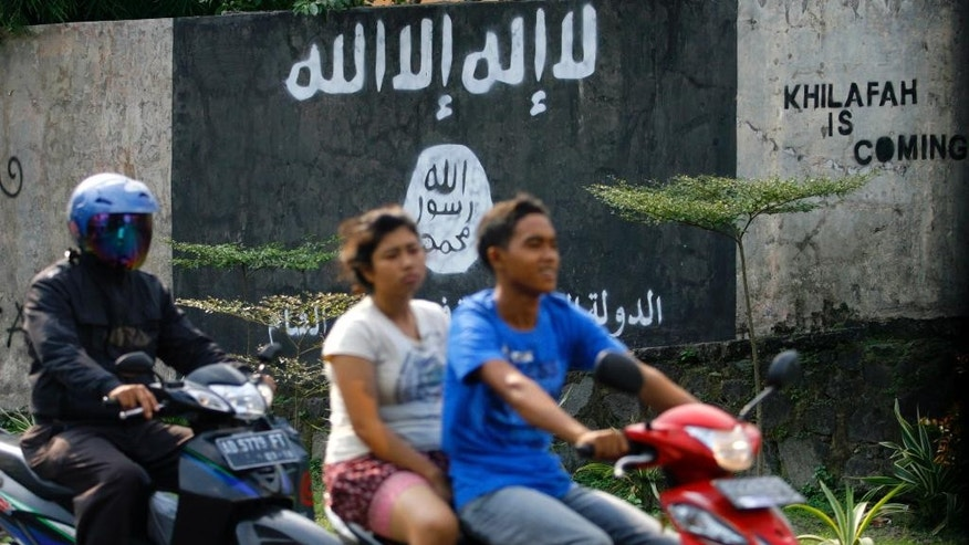 In this March 8, 2014 photo, motorists ride past a graffiti of the Islamic State group's flag in Solo, Central Java, Indonesia. The world's largest Muslim country is facing a new threat as security officials fear that militants who are joining the Islamic State could take part in terrorism acts on their return to Southeast Asia. (AP Photo)