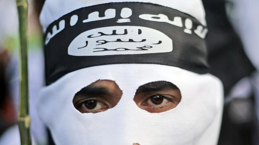 In this June 18, 2014 photo, a Muslim man wears a headband showing the Islamic State group's symbol during a protest calling for the closure of a local prostitution complex in Surabaya, Indonesia. The world's largest Muslim country is facing a new threat as security officials fear that militants who are joining the Islamic State could take part in terrorism acts on their return to Southeast Asia. (AP Photo/Dita Alangkara)