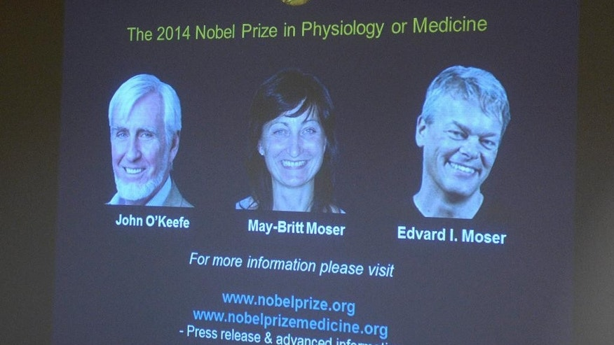 Images of the winners of the  2014 Nobel Prize for Medicine, U.S.-British scientist John O'Keefe and Norwegian husband and wife Edvard Moser and May-Britt Moser are projected on a screen during the announcement in Stockholm Monday Oct. 6, 2014.(AP Photo/Bertil Ericson)  SWEDEN OUT